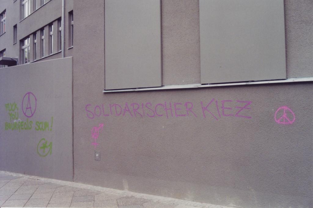 "Graue Neubauwand mit dem Schriftzug ""Solidarischer Kiez"""