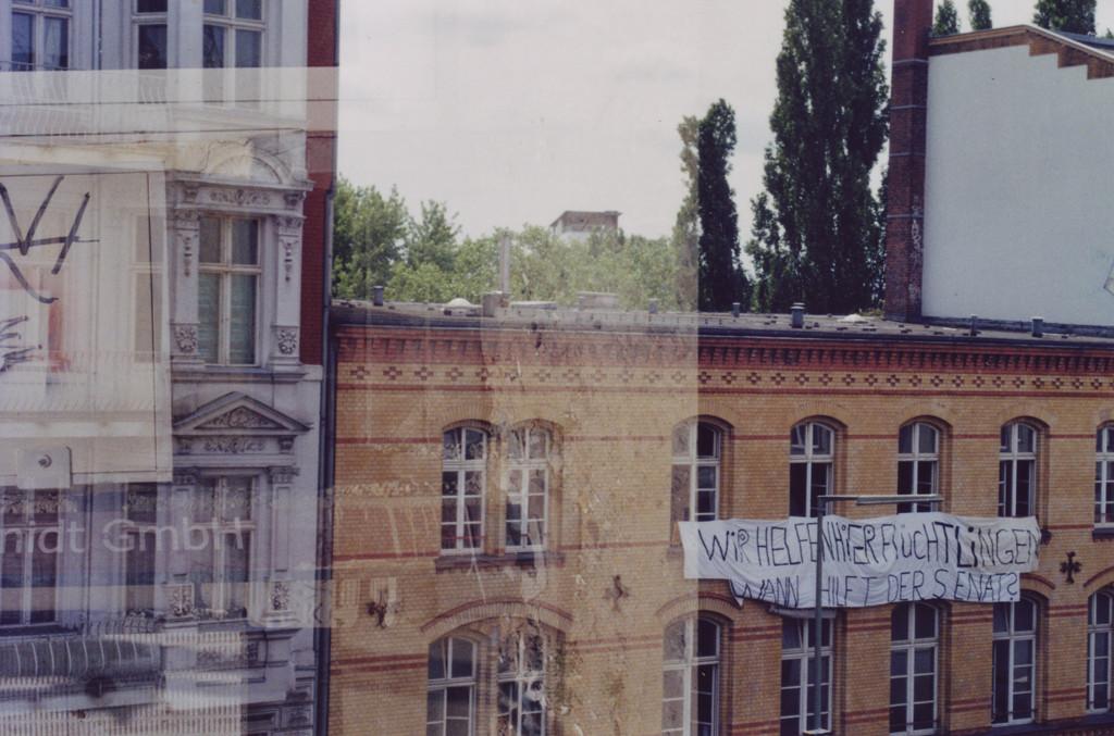Blick aus dem Fenster auf ein Haus auf der anderen Strassenseite, dort ein Banner: Wir helfen hier Flüchtlingen, wann hilft der Senat (Gitschiner 15)