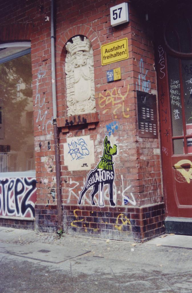 """Streetart an einer Backsteinmauer: Ein stilisierter Hund (Dobermann) mit der Aufschrift """"Real Estate Speculators"""""""