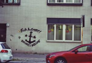 Graffiti, Text um einen Anker: Fuck Austerity, Refugees welcome